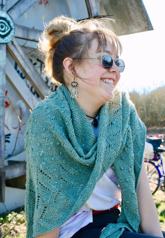 Handknitted Shawl wrapped around the neck of white girl wearing sunglasses. In the background a wall with graffiti.