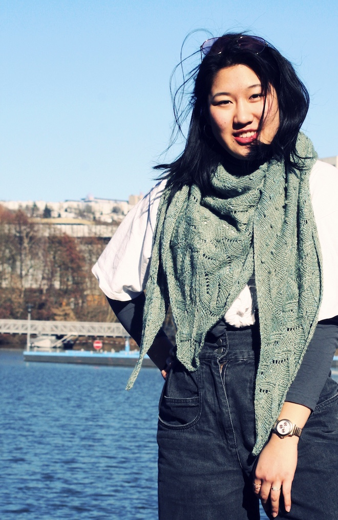 Immersion shawl wrapped around neck of Chinese girl smiling to the camera. In the background cityscape with river.